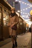 Νέα γυναίκα σε ένα παλτό για έναν περίπατο στην πόλη, στοκ εικόνα