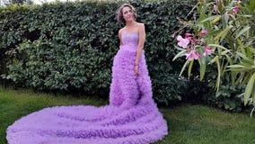 Νέα γυναίκα σε ένα ρόδινο φόρεμα με μια μακροχρόνια τοποθέτηση τραίνων φιλμ μικρού μήκους