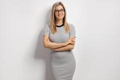 Νέα γυναίκα σε ένα φόρεμα που κλίνει ενάντια σε έναν άσπρο τοίχο Στοκ Εικόνα