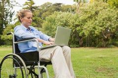 Νέα γυναίκα σε μια αναπηρική καρέκλα με ένα lap-top Στοκ Εικόνες