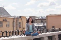 Νέα γυναίκα σε μια θέση λωτού στο στηθαίο Στοκ εικόνες με δικαίωμα ελεύθερης χρήσης