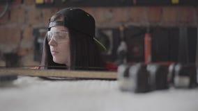 Νέα γυναίκα σε μια ΚΑΠ και προστατευτικά γυαλιά με το διαπερασμένο χείλι και δαχτυλίδι στη μύτη που μετρά το μήκος του MDF πιάτου απόθεμα βίντεο