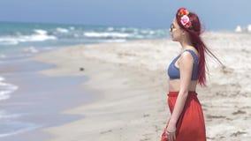 Νέα γυναίκα σε μια κόκκινη φούστα και μπλε κορυφή με την κόκκινη τρίχα που πετά στον αέρα και ένα floral στεφάνι στην τρίχα της ε απόθεμα βίντεο