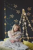 Νέα γυναίκα σε μια τοποθέτηση καρό στα πλαίσια των γιρλαντών Χριστουγέννων στοκ φωτογραφία με δικαίωμα ελεύθερης χρήσης