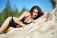 Νέα γυναίκα σε μια τοποθέτηση μαγιό υπαίθρια σε έναν φωτεινό ήλιο Στοκ Φωτογραφίες