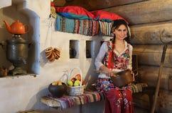 Νέα γυναίκα σε μια χαρακτηριστική ρωσική ξύλινη καλύβα κούτσουρων Στοκ εικόνα με δικαίωμα ελεύθερης χρήσης