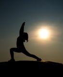 Νέα γυναίκα σκιαγραφιών που ασκεί yogaอ με την ανατολή Στοκ Φωτογραφία