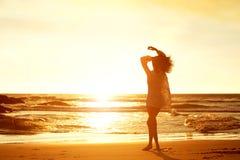 Νέα γυναίκα σκιαγραφιών που περπατά στην παραλία κατά τη διάρκεια του ηλιοβασιλέματος Στοκ εικόνες με δικαίωμα ελεύθερης χρήσης