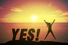 Νέα γυναίκα σκιαγραφιών που πηδά και που αυξάνει επάνω στο χέρι όπως την ευτυχή έννοια στο κείμενο επιτυχίας Στοκ Εικόνα