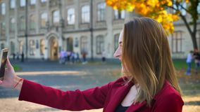 Νέα γυναίκα σπουδαστής που έχει μια τηλεοπτική κλήση στο τηλέφωνό της και που είναι σε μια καλή διάθεση, έξω από το πανεπιστήμιο, απόθεμα βίντεο