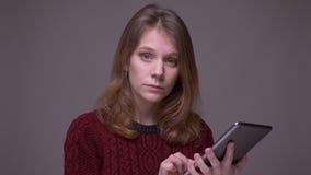 Νέα γυναίκα σπουδαστής που εργάζεται με την ταμπλέτα που είναι προσεκτικές και συγκεντρωμένες στροφές στη κάμερα στο γκρίζο υπόβα φιλμ μικρού μήκους