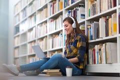 Νέα γυναίκα σπουδαστής που μελετά στη βιβλιοθήκη Στοκ φωτογραφία με δικαίωμα ελεύθερης χρήσης