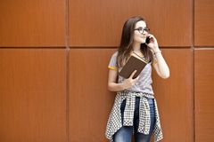 Νέα γυναίκα σπουδαστής που μιλά στο τηλέφωνο υπαίθρια στοκ φωτογραφίες
