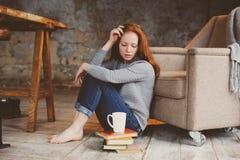 Νέα γυναίκα σπουδαστών readhead που μαθαίνει και που διαβάζει τα βιβλία στοκ εικόνες