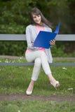 Νέα γυναίκα σπουδαστής με το αρχείο που κάθεται σε έναν πάγκο, υπαίθρια Στοκ φωτογραφία με δικαίωμα ελεύθερης χρήσης