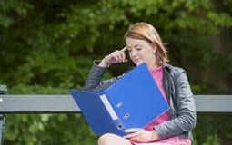 Νέα γυναίκα σπουδαστής με το αρχείο που κάθεται σε έναν πάγκο, υπαίθρια Στοκ εικόνα με δικαίωμα ελεύθερης χρήσης