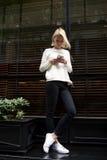 Νέα γυναίκα σπουδαστής που δακτυλογραφεί ένα μήνυμα κειμένου ή που κοιτάζει βιαστικά Διαδίκτυο στο κινητό τηλέφωνο της Στοκ Εικόνα