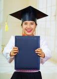 Νέα γυναίκα σπουδαστής που φορά το παραδοσιακό καπέλο μπλουζών και βαθμολόγησης, κρατώντας το μαύρο βιβλιάριο διπλωμάτων, που χαμ Στοκ Εικόνα
