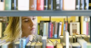 Νέα γυναίκα σπουδαστής που ψάχνει το βιβλίο στη σχολική βιβλιοθήκη απόθεμα βίντεο