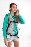 Νέα γυναίκα σπουδαστής brunette που στέκεται και που ακούει τη μουσική από τη συσκευή σας Στοκ φωτογραφία με δικαίωμα ελεύθερης χρήσης
