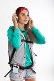 Νέα γυναίκα σπουδαστής brunette που στέκεται και που ακούει τη μουσική από τη συσκευή σας Στοκ εικόνες με δικαίωμα ελεύθερης χρήσης