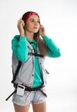 Νέα γυναίκα σπουδαστής brunette που στέκεται και που ακούει τη μουσική από τη συσκευή σας Στοκ εικόνα με δικαίωμα ελεύθερης χρήσης