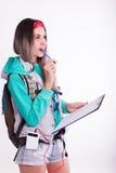 Νέα γυναίκα σπουδαστής brunette που στέκεται και που ακούει τη μουσική από τη συσκευή σας Στοκ Εικόνες