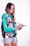 Νέα γυναίκα σπουδαστής brunette που στέκεται και που ακούει τη μουσική από τη συσκευή σας Στοκ Φωτογραφία