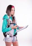 Νέα γυναίκα σπουδαστής brunette που στέκεται και που ακούει τη μουσική από τη συσκευή σας Στοκ Φωτογραφίες