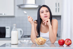 Νέα γυναίκα στα άσπρα ενδύματα που κάθεται στην κουζίνα στοκ εικόνα με δικαίωμα ελεύθερης χρήσης