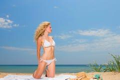 Νέα γυναίκα στα άσπρα σαρόγκ εκμετάλλευσης μπικινιών στην παραλία Στοκ φωτογραφία με δικαίωμα ελεύθερης χρήσης