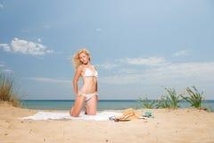 Νέα γυναίκα στα άσπρα σαρόγκ εκμετάλλευσης μπικινιών στην παραλία Στοκ Φωτογραφίες