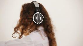 Νέα γυναίκα στα ακουστικά και το άσπρο άκουσμα πουκάμισων φιλμ μικρού μήκους
