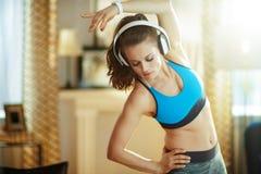 Νέα γυναίκα στα ακουστικά στο σύγχρονο εγχώριο τέντωμα στοκ εικόνα