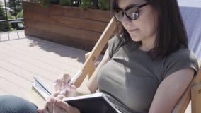 Νέα γυναίκα στα γυαλιά ηλίου που παίρνουν τις σημειώσεις στο σημειωματάριο υπαίθρια απόθεμα βίντεο