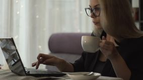 Νέα γυναίκα στα γυαλιά που λειτουργούν στη συνεδρίαση σημειωματάριων στον καναπέ και τον καφέ κατανάλωσης φιλμ μικρού μήκους