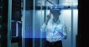 Νέα γυναίκα στα γυαλιά VR που λειτουργούν σε ένα κέντρο δεδομένων απόθεμα βίντεο