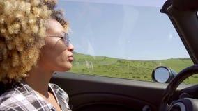 Νέα γυναίκα στα γυαλιά ηλίου που οδηγούν το αυτοκίνητό της φιλμ μικρού μήκους