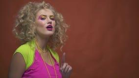 Νέα γυναίκα στα ενδύματα της δεκαετίας του '80 που είναι flirty απόθεμα βίντεο