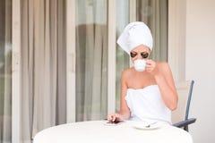 Νέα γυναίκα στα μπαλώματα κάτω από-ματιών που γράφουν sms το μήνυμα και που πίνουν τον καφέ στο θέρετρο πεζουλιών ξενοδοχείων ένν στοκ φωτογραφίες