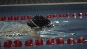 Νέα γυναίκα στα προστατευτικά δίοπτρα που κολυμπούν το πρόσθιο στην μπλε πισίνα νερού απόθεμα βίντεο