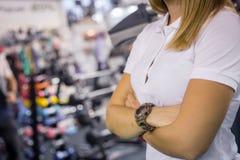 Νέα γυναίκα στην άσπρη μπλούζα με το ρολόι στο βραχίονά της με τη θολωμένη γυμναστική στο υπόβαθρο στοκ φωτογραφία