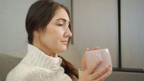 Νέα γυναίκα στην άσπρη συνεδρίαση πουλόβερ στον καναπέ και και τον καφέ κατανάλωσης στο σπίτι απόθεμα βίντεο