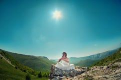 Νέα γυναίκα στην άσπρη συνεδρίαση φλαούτων φορεμάτων παίζοντας σε ένα βουνό ρ Στοκ φωτογραφίες με δικαίωμα ελεύθερης χρήσης