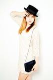 Νέα γυναίκα στην άσπρη τοποθέτηση φορεμάτων και μαύρων καπέλων Στοκ Εικόνες