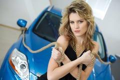 Νέα γυναίκα στην αίθουσα εκθέσεως με ένα νέο αυτοκίνητο με το ro Στοκ Εικόνα