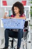 Νέα γυναίκα στην αναπηρική καρέκλα με το καλάθι πλυντηρίων Στοκ Φωτογραφία