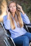 Νέα γυναίκα στην αναπηρική καρέκλα που ακούει τη μουσική Στοκ Φωτογραφίες