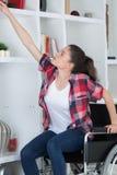 Νέα γυναίκα στην αναπηρική καρέκλα που επιλέγει το βιβλίο στη βιβλιοθήκη Στοκ φωτογραφία με δικαίωμα ελεύθερης χρήσης
