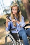 Νέα γυναίκα στην αναπηρική καρέκλα strolling στα ξύλα Στοκ φωτογραφία με δικαίωμα ελεύθερης χρήσης